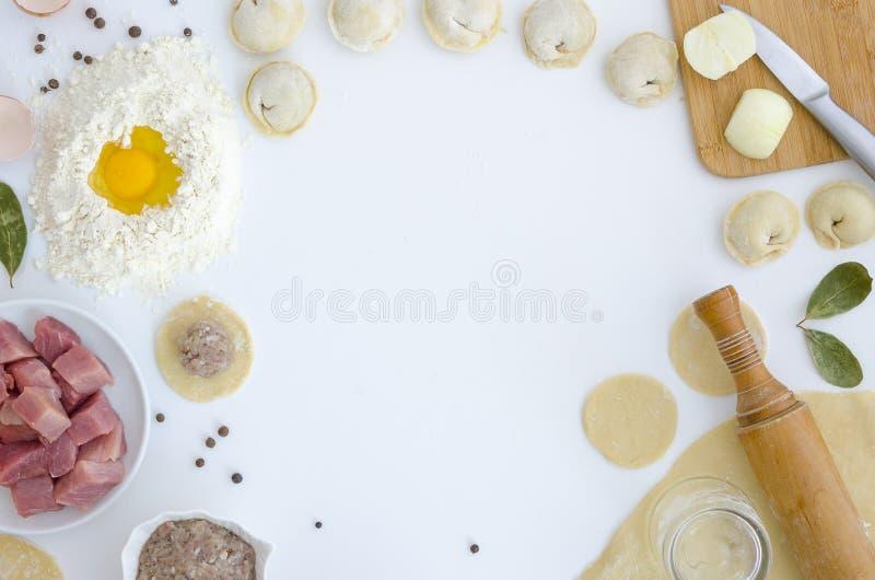 Cocinar el marco ruso tradicional del fondo de las bolas de masa hervida del pelmeni Ingredientes, art?culos de la cocina para lo foto de archivo libre de regalías