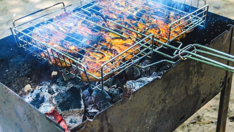 Cocinar el pollo asado a la parrilla en los carbones calientes imagen de archivo