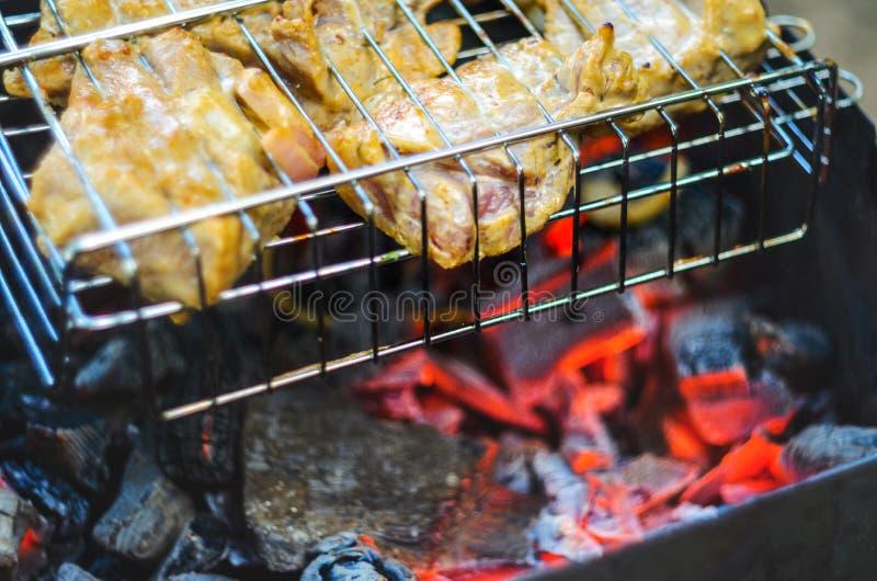 Cocinar el pollo asado a la parrilla en los carbones calientes fotos de archivo