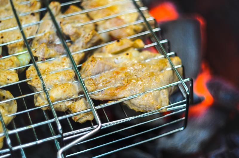 Cocinar el pollo asado a la parrilla en los carbones calientes foto de archivo libre de regalías