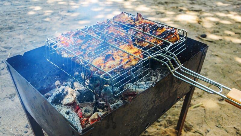 Cocinar el pollo asado a la parrilla en los carbones calientes imagenes de archivo