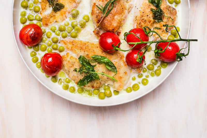 Cocinar la cacerola con la pechuga de pollo, el guisante verde y los tomates de la carne asada en salsa cremosa en el fondo de ma fotos de archivo libres de regalías