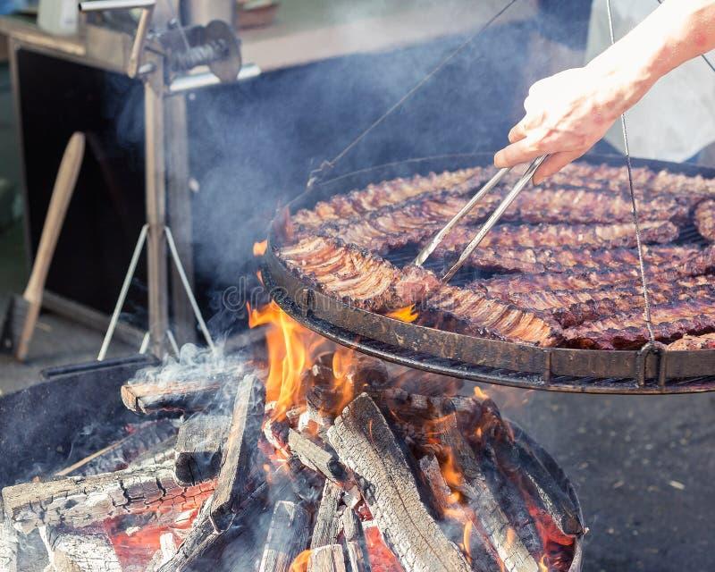 Cocinar la carne en la parrilla en el mercado de la comida de la calle fotos de archivo