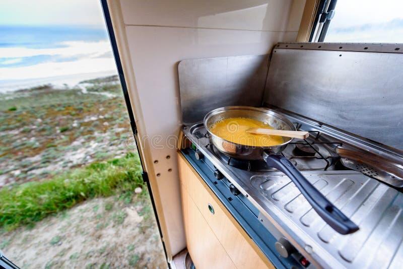 Cocinar la cena o el desayuno en motorhome del campista con la opinión de la playa imágenes de archivo libres de regalías