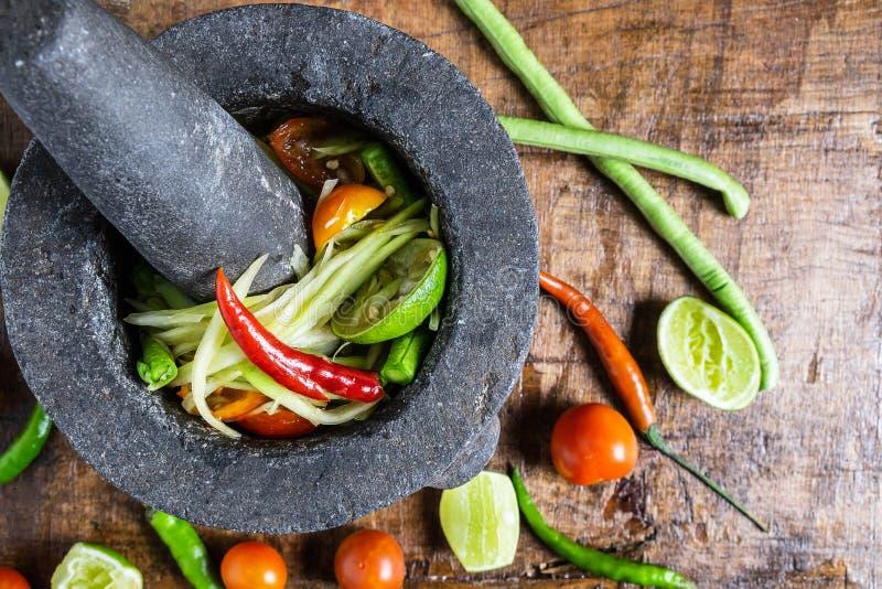 Cocinar la comida, la ensalada de la papaya y el aderezo tailandeses en una tabla de madera fotografía de archivo libre de regalías