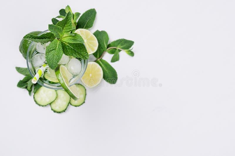 Cocinar la limonada orgánica del verano fresco con las rebanadas pepino, hielo, cal, menta, paja en el fondo de madera blanco, vi fotografía de archivo