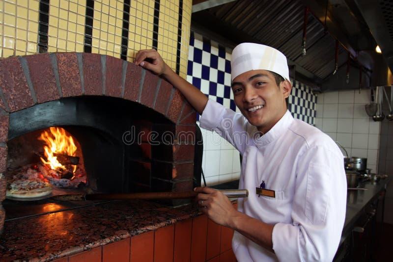 Cocinar la pizza foto de archivo