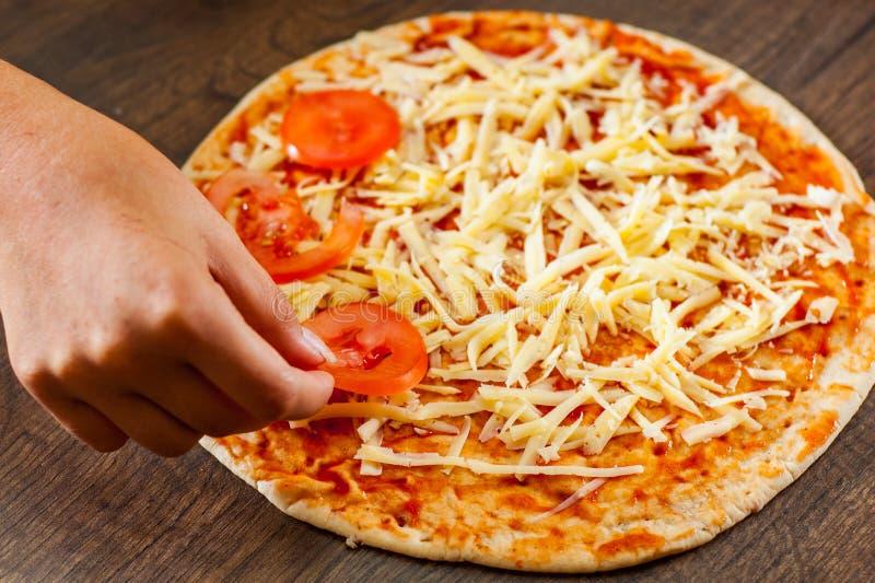 Cocinar la pizza el cocinero de la mujer de la mano pone la rebanada del tomate en la pasta fabricación de la pizza italiana fotos de archivo