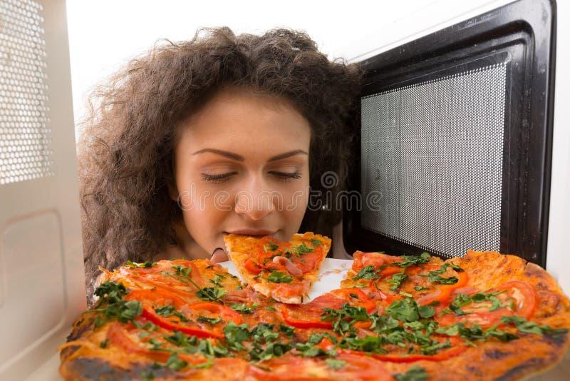 Cocinar la pizza en la microonda foto de archivo libre de regalías