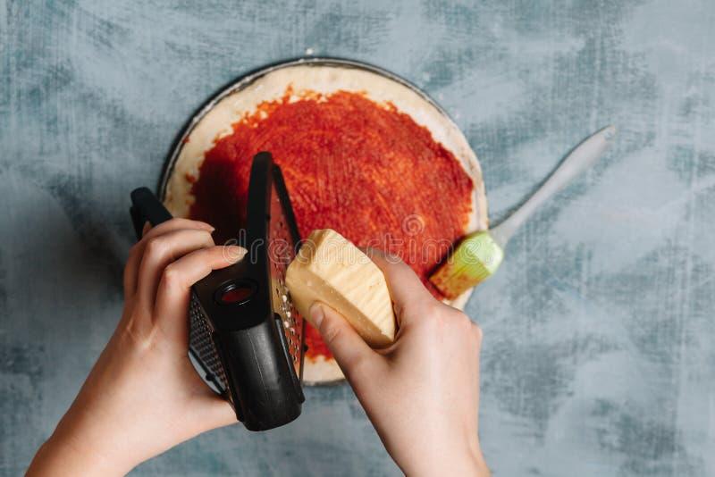 Cocinar la pizza italiana con los tomates, pollo, aceitunas en fondo de madera Salsa de tomate en la pasta por la mano de la muje fotos de archivo