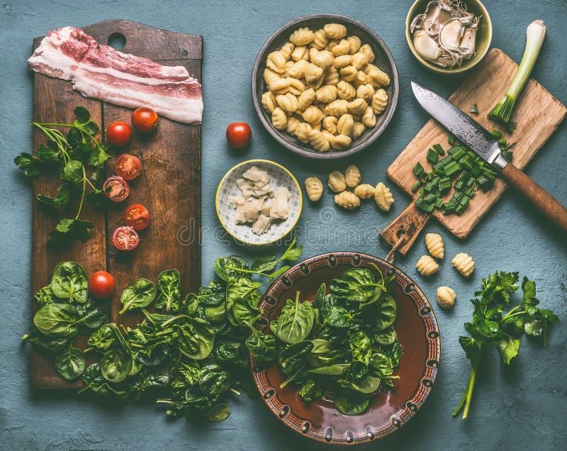 Cocinar la preparación de la comida del gnocchi de la patata con espinaca, los tomates y el tocino en la tabla rústica imagen de archivo libre de regalías