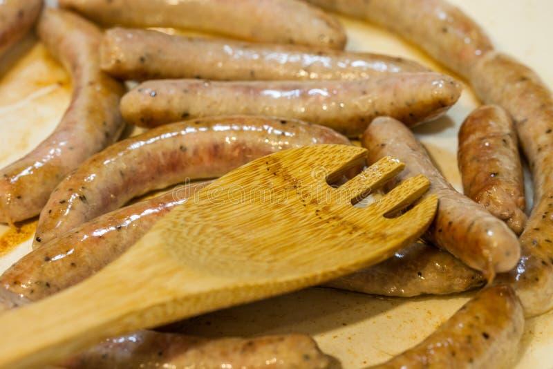 Cocinar la salchicha del desayuno liga en un sartén a la cuchara de madera imagenes de archivo
