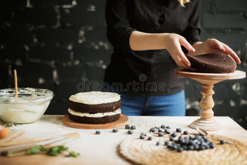 Cocinar la torta en la tabla y cocer los ingredientes de la torta imagen de archivo libre de regalías