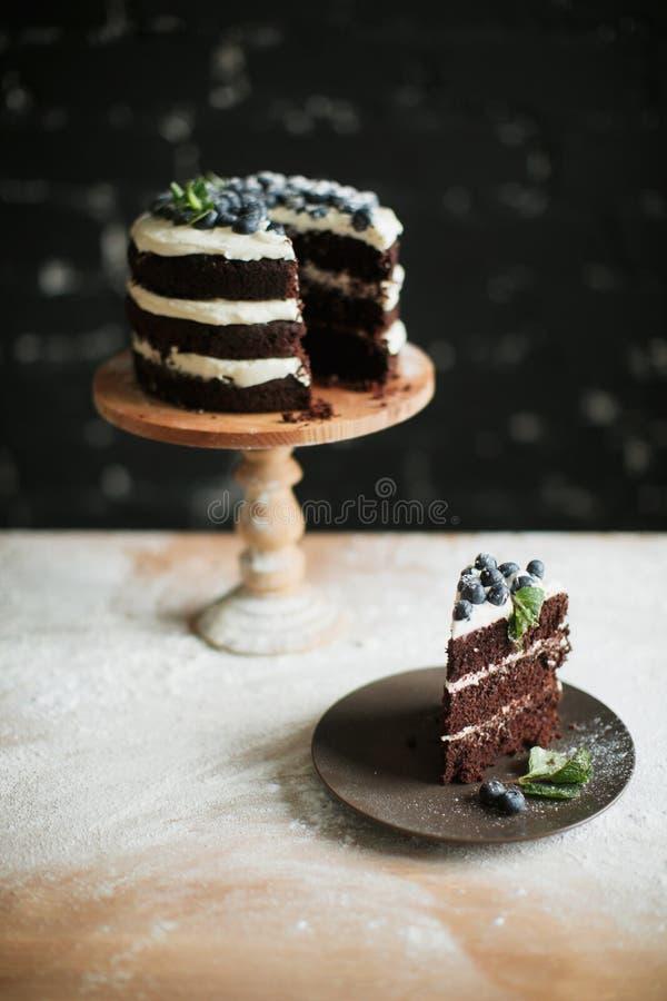 Cocinar la torta en la tabla y cocer los ingredientes de la torta imagen de archivo