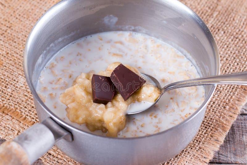 Cocinar las gachas de avena de la harina de avena del chocolate en un cazo foto de archivo