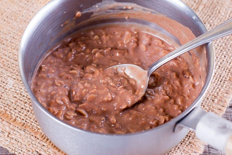 Cocinar las gachas de avena de la harina de avena del chocolate en un cazo fotos de archivo