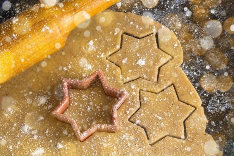 Cocinar las galletas del pan de jengibre de la Navidad con el rodillo en un fondo oscuro foto de archivo libre de regalías