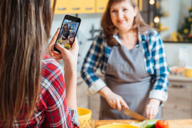Cocinar a las mujeres del blog que cortan smartphone de las verduras fotografía de archivo