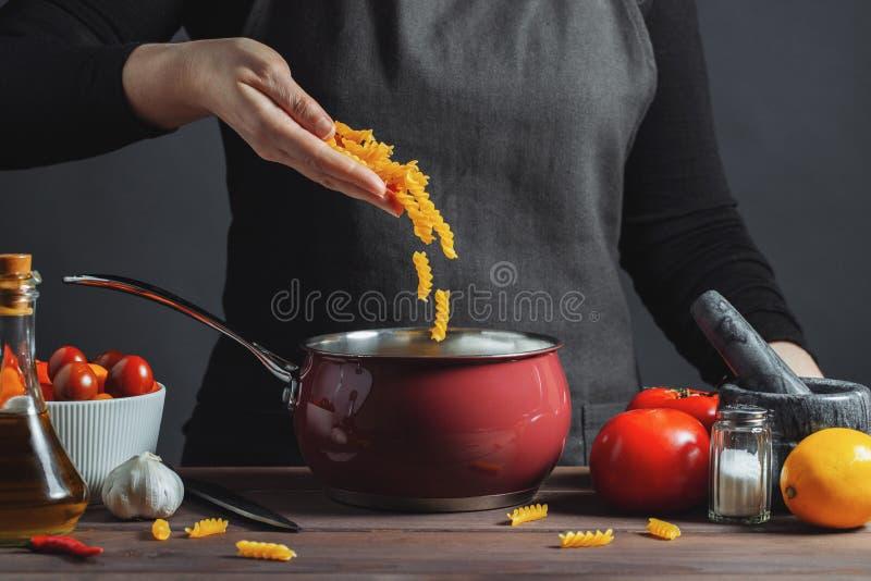 Cocinar las pastas italianas en un pote en la cocina, cocinero que prepara la comida, comida El cocinero de la mujer- lanza en el foto de archivo libre de regalías