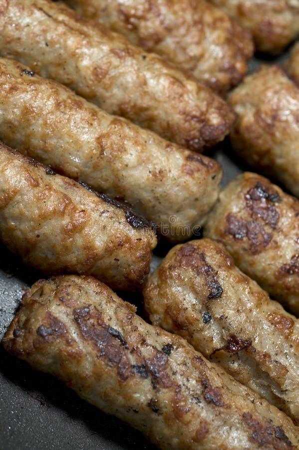 Cocinar las salchichas en una cacerola imagen de archivo