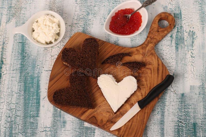 Cocinar los bocadillos con el caviar y el queso cremoso rojos en la forma de un corazón para el día de tarjeta del día de San Val fotos de archivo