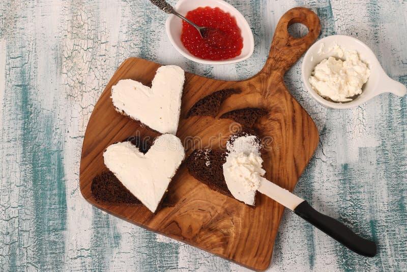 Cocinar los bocadillos con el caviar y el queso cremoso rojos en la forma de un corazón para el día de tarjeta del día de San Val foto de archivo libre de regalías