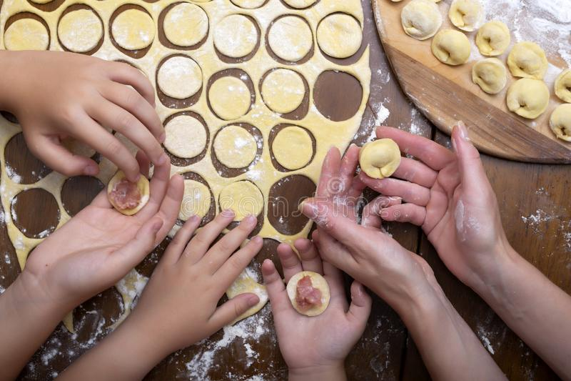 Cocinar los raviolis de la pasta y de la carne con la familia entera Mujeres y las manos de los niños Bolas de masa hervida hecha imagen de archivo
