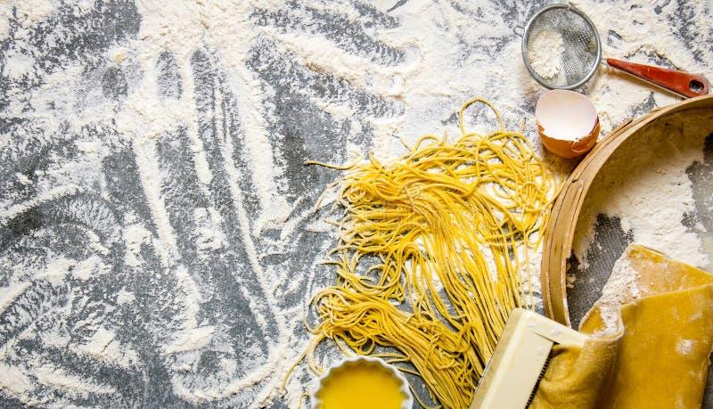 Cocinar los tallarines El fabricante de las pastas con el tamiz, los huevos y la harina foto de archivo