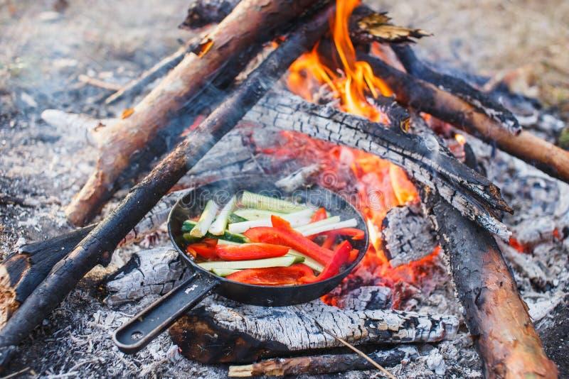 Cocinar platos de los paprikas y de los pepinos rojos en una cacerola en un fuego fotos de archivo libres de regalías