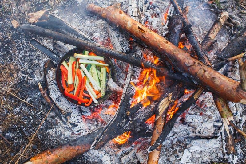 Cocinar platos de los paprikas y de los pepinos rojos en una cacerola en un fuego imagen de archivo