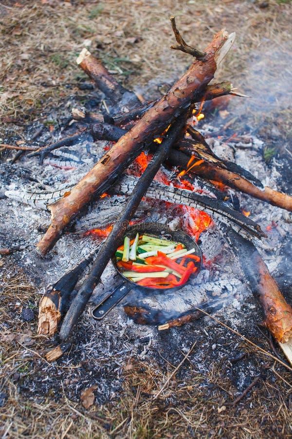 Cocinar platos de los paprikas y de los pepinos rojos en una cacerola en un fuego fotos de archivo