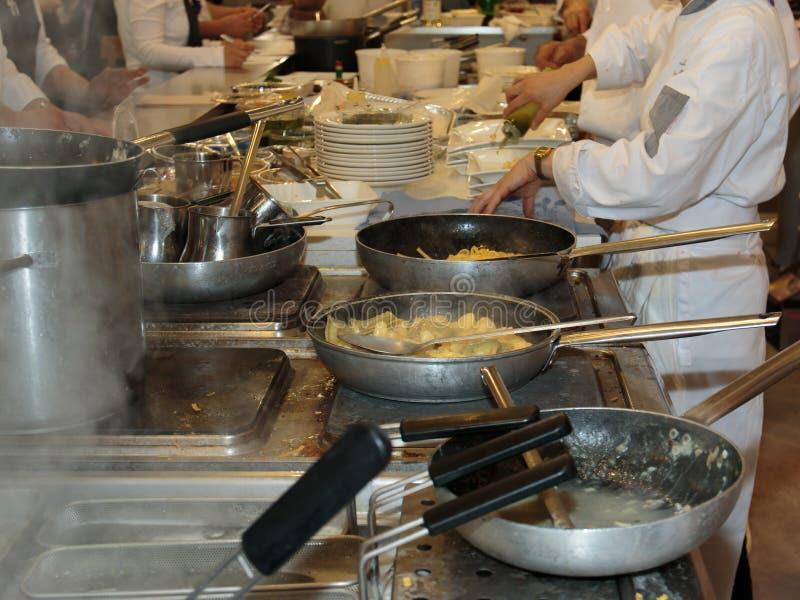 Cocinar Restaurant& interior x27; cocina, cacerolas y cocinero de s con el uniforme foto de archivo libre de regalías