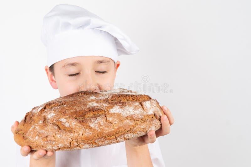 Cocine a Boy With Bread en el fondo blanco imagen de archivo libre de regalías