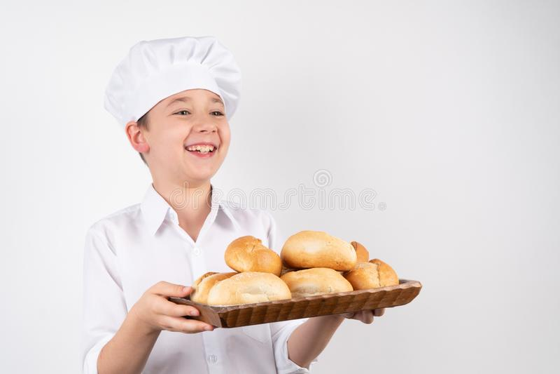 Cocine a Boy With Bread en el fondo blanco, risas foto de archivo