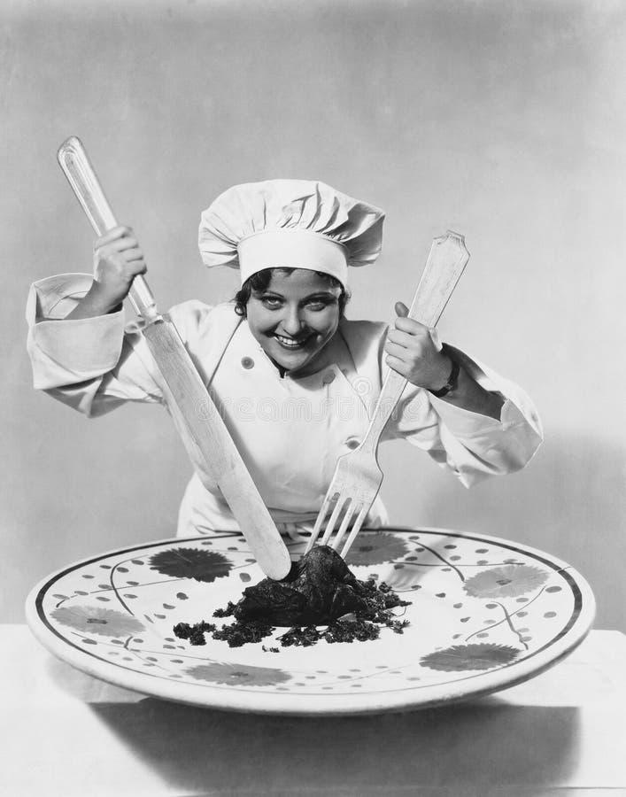Cocine con la comida en la placa de gran tamaño con los utensilios de gran tamaño (todas las personas representadas no son vivas  imágenes de archivo libres de regalías