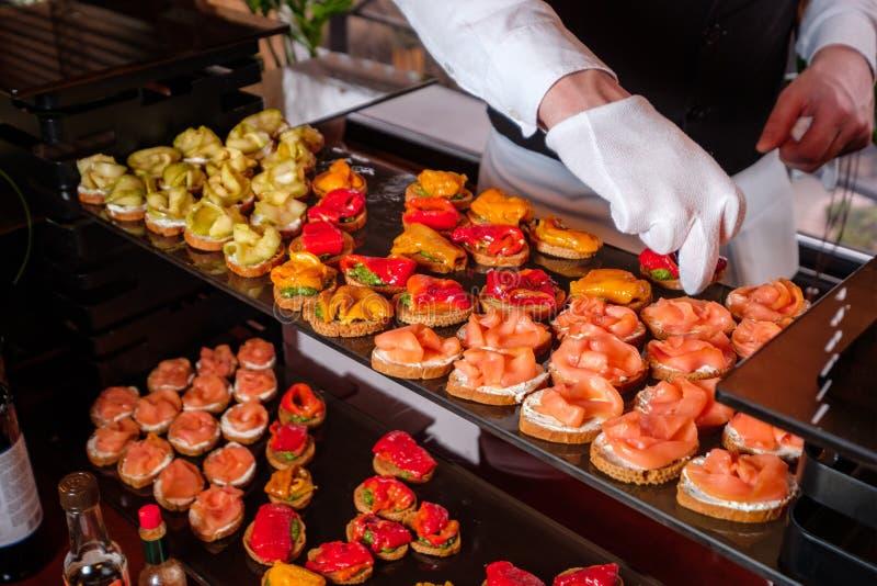 Cocine el primer, pone hacia fuera los bocados de verduras y de la carne a un buffet en el restaurante foto de archivo