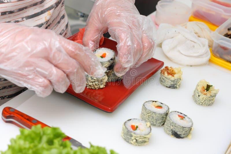 Cocine en el susi de Japón de la porción de la cocina en la placa foto de archivo