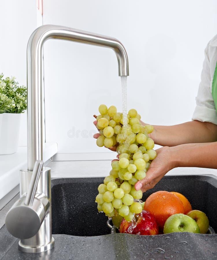 Cocine a la mujer lava un manojo de uvas debajo del agua que fluye de un golpecito imagenes de archivo