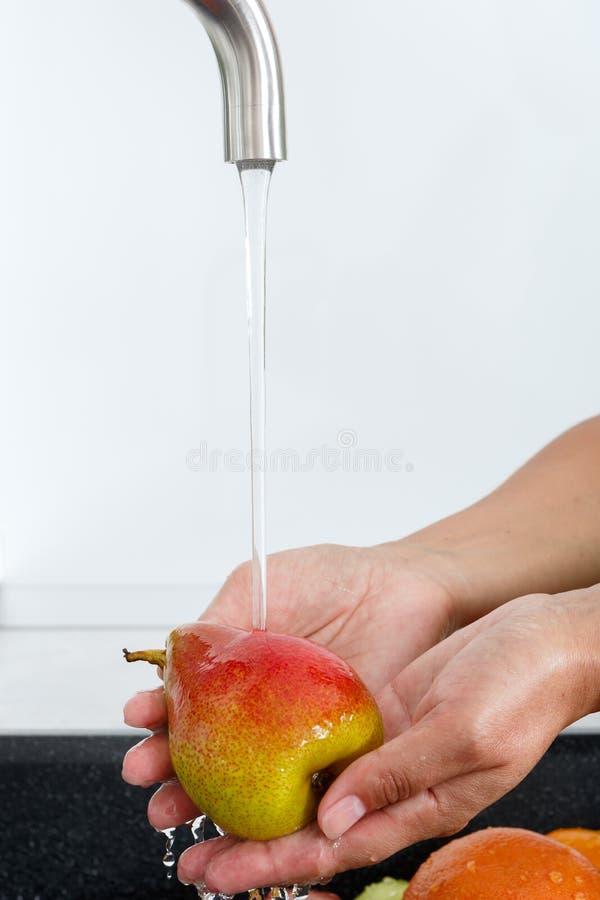 Cocine a la mujer lava una pera debajo del agua que fluye de un golpecito de agua fotos de archivo libres de regalías