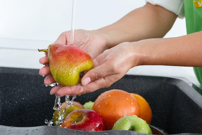 Cocine a la mujer lava una pera debajo del agua que fluye de un golpecito de agua imágenes de archivo libres de regalías