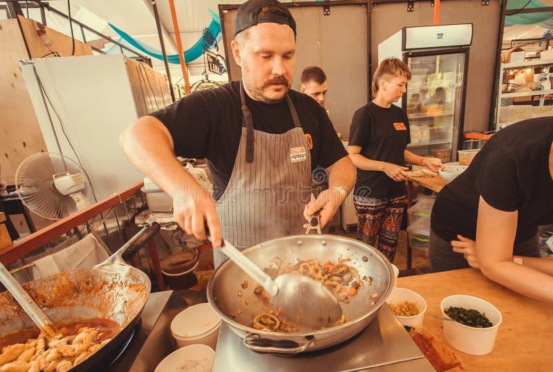 Cocine la preparación de la comida tailandesa con las especias y las verduras en un wok enorme fotos de archivo libres de regalías