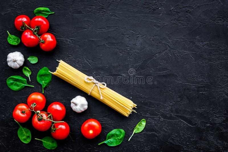 Cocine los espaguetis con los tomates, ajo, albahaca Receta italiana Espacio de madera negro de la copia de la opinión superior d fotografía de archivo libre de regalías