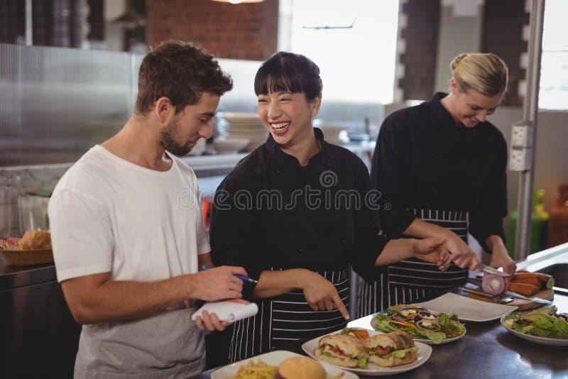 Cocinero alegre que señala en la comida al camarero del colega femenino fotos de archivo libres de regalías