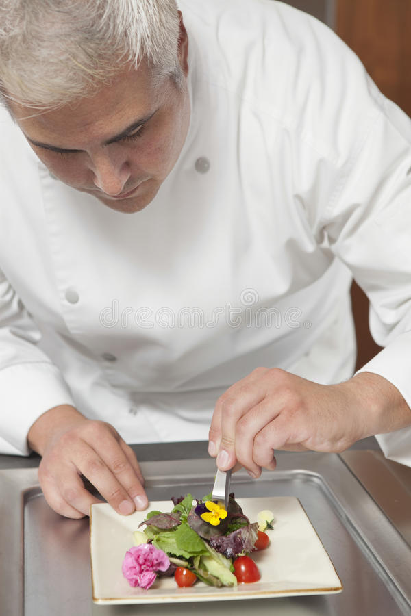 Cocinero Arranging Edible Flowers en la ensalada fotografía de archivo libre de regalías