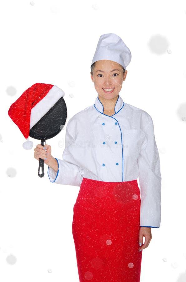 Cocinero asiático con el sartén y el sombrero de la Navidad foto de archivo