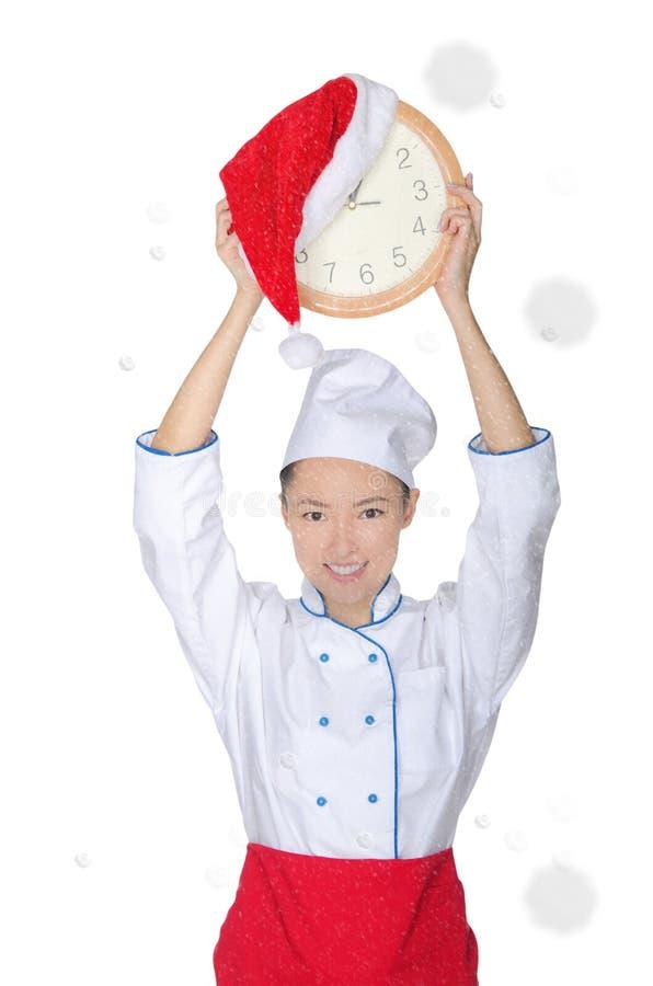 Cocinero asiático feliz con el reloj y el sombrero de la Navidad imagenes de archivo