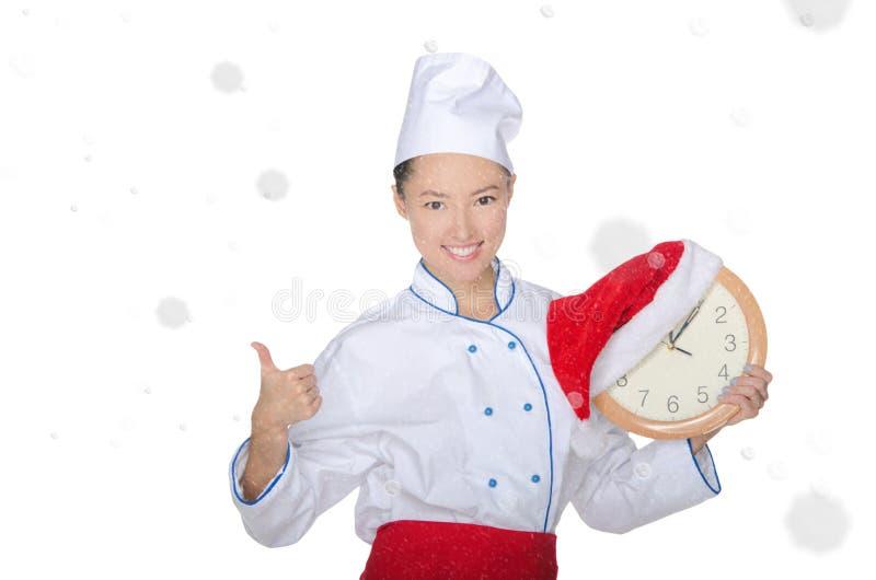 Cocinero asiático hermoso con el reloj y el sombrero de la Navidad imagenes de archivo