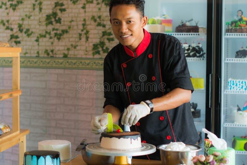 Cocinero asiático profesional de la parte que adorna la torta que pone la cereza roja fotos de archivo