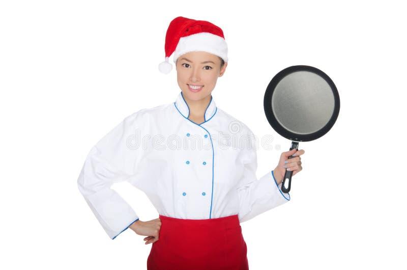 Cocinero asiático sonriente con el sartén y el sombrero de la Navidad imagen de archivo