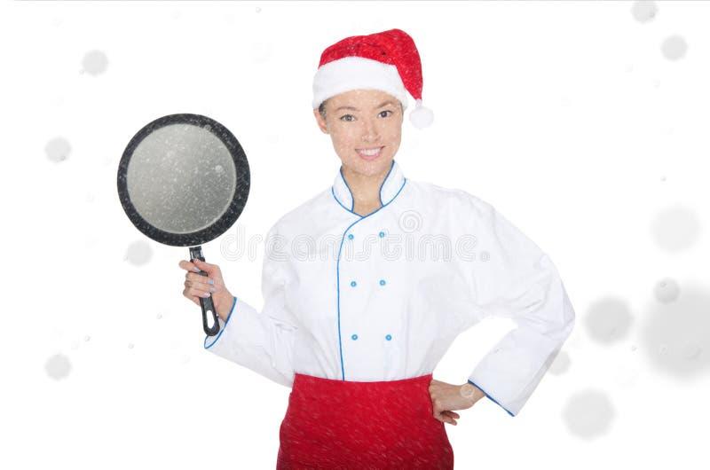 Cocinero asiático sonriente con el sartén y el sombrero de la Navidad foto de archivo libre de regalías